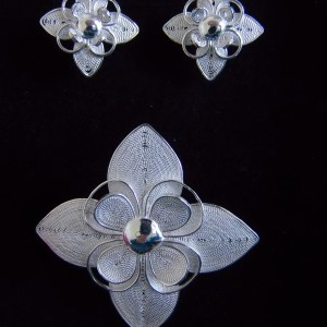 Délicate parure de trois bijoux: une paire de clous d'oreille et sa broche qui peut être portée en pendentif.