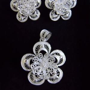 Coquette parure composée d'une paire de clous fleurs et d'u pendentif orné du même motif, le tout brodé d'un enchevêtrement de ils d'argent.