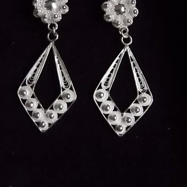 Jolie paire de boucles d'oreille pendantes composée d'un clou en forme de fleur à laquelle est suspendue un losange sculpté en fils d'argent.