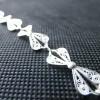Un bracelet fin composé de petits noeuds en fil d'argent